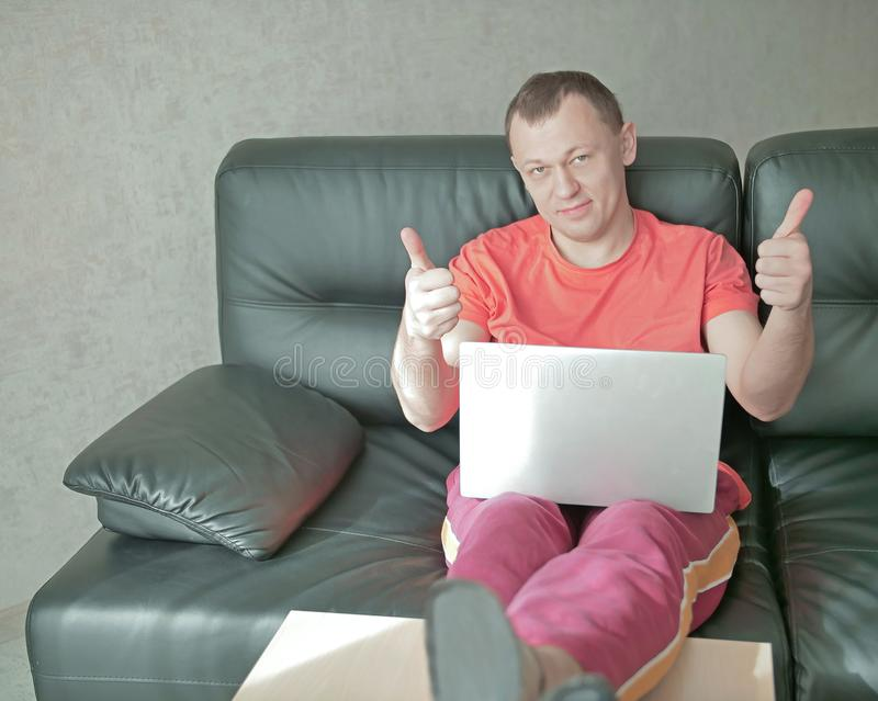Young smiling man with laptop sits on sofa at home and holds thumbs up, looks into camera stock images
