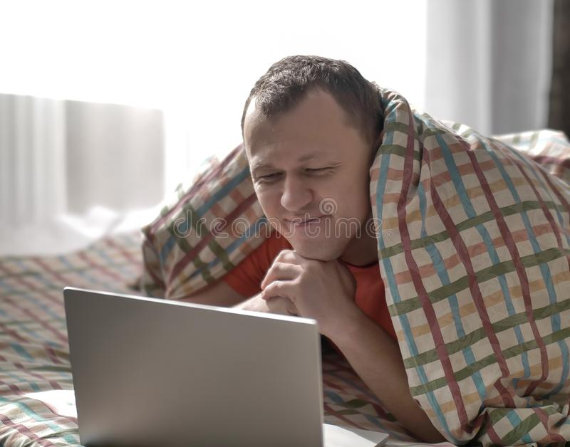 Young smiling man is lying on the bed, looking into the laptop royalty free stock photography