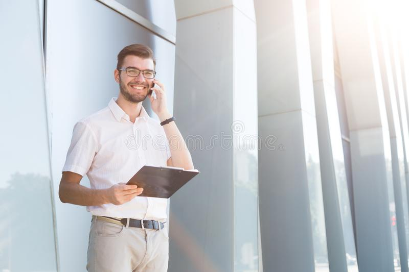 Young smiling man making a call and holding clipboard stock photo