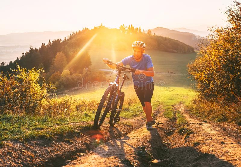 Young smiling man pushing a mountain bike up the hill. Active adventure travel on bicycle stock photos