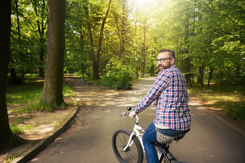 Young smiling man riding bike in park turning back stock images