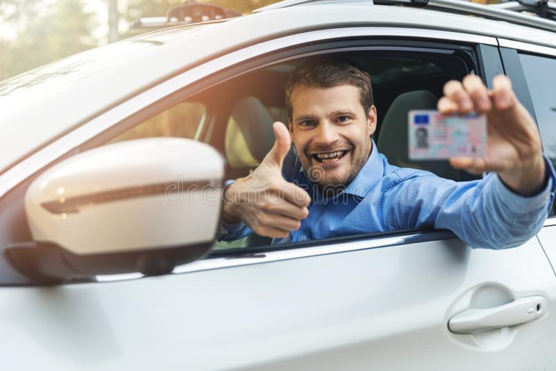 Young smiling man sitting in the car and showing his new driver license with thumb up sign royalty free stock photos