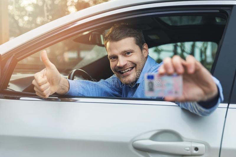 Young smiling man sitting in the car and showing his new driver license with thumb up sign royalty free stock photo