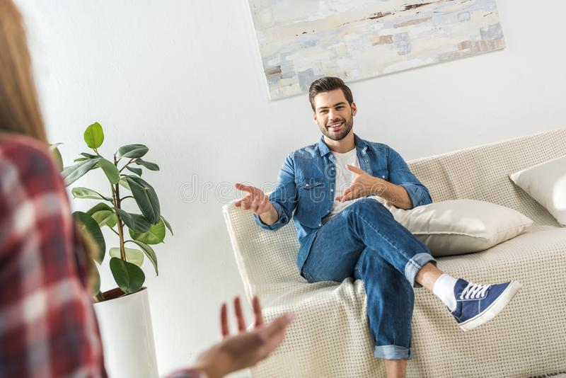 Young smiling man sitting on sofa at home while talking to. A woman royalty free stock images