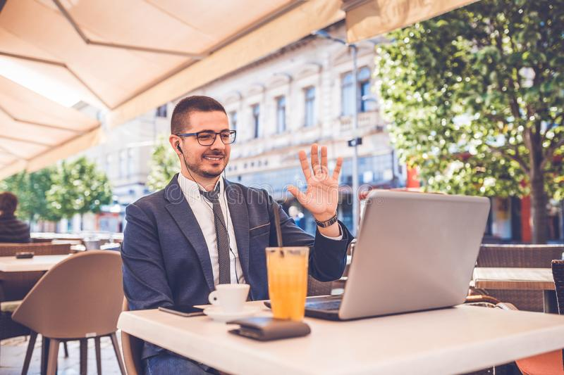 Young man sitting at street cafe waving his hand to camera on laptop while having video call stock photos