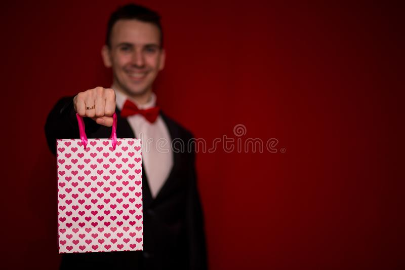 Young smiling man in suit hold love gift bag royalty free stock images