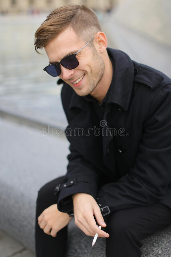 Free Young Smiling Man Wearing Black Jacket Sitting On Louvre Pyramid And Smoking. Stock Images - 187215634