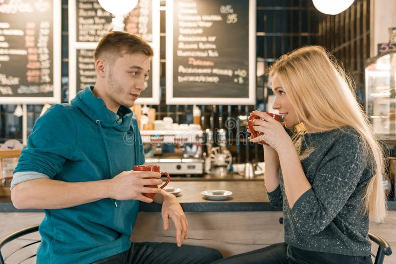 Young smiling man and woman together talking in coffee shop sitting near bar counter, couple of friends drinking tea, coffee royalty free stock images