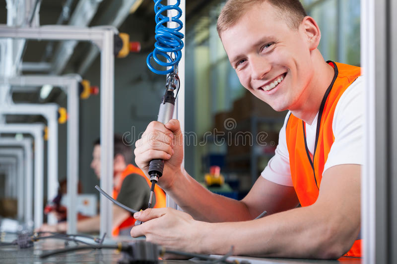 Young smiling man working on the production line royalty free stock image