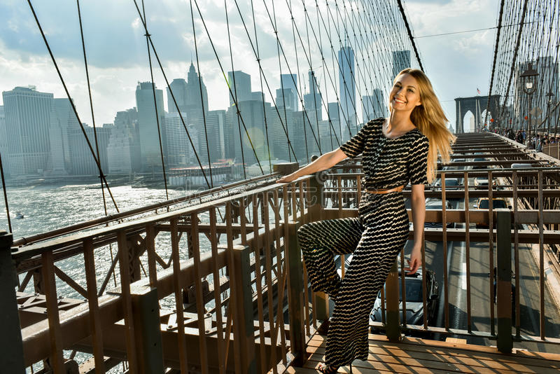 Young smiling model posing at the bridge in hot summer day wearing fashionable jumpsuit. Young smiling model with long blonde hair posing at the bridge in hot royalty free stock photography