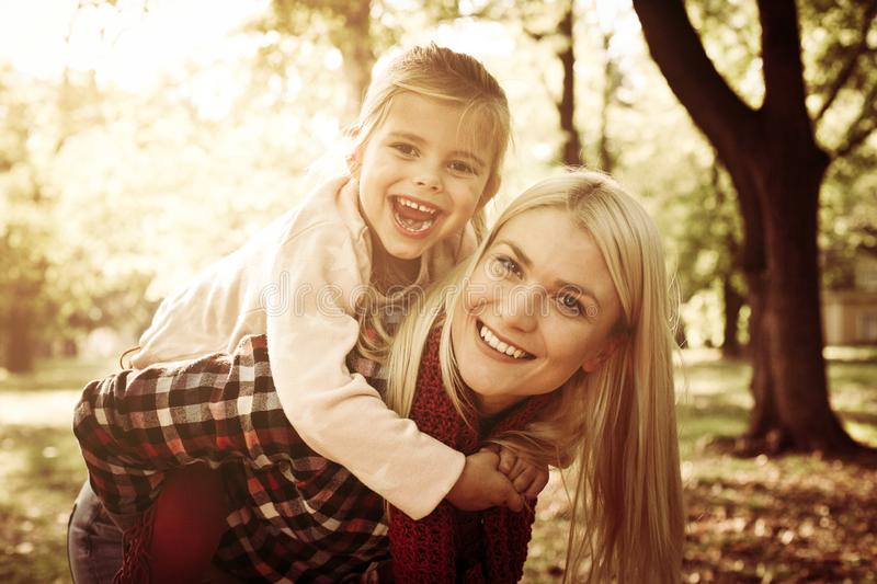 Smiling mother and her daughter in park. Mother carrying her daughter on piggyback. stock photo