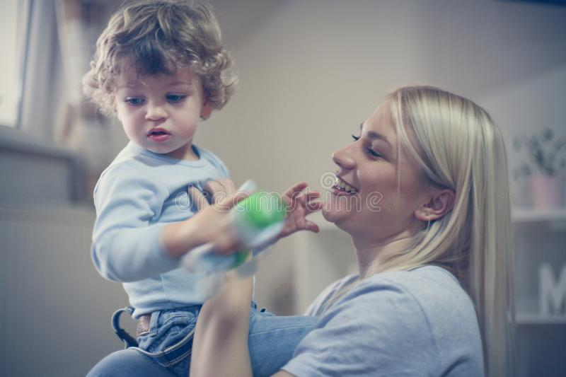 Young smiling mother playing with her baby boy. stock image