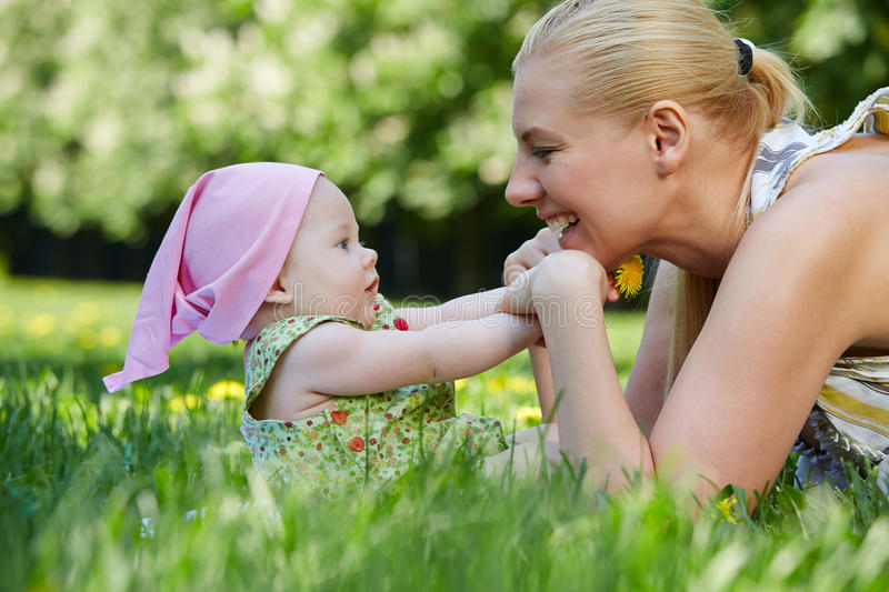 Young mother plays with her baby on grass stock photos
