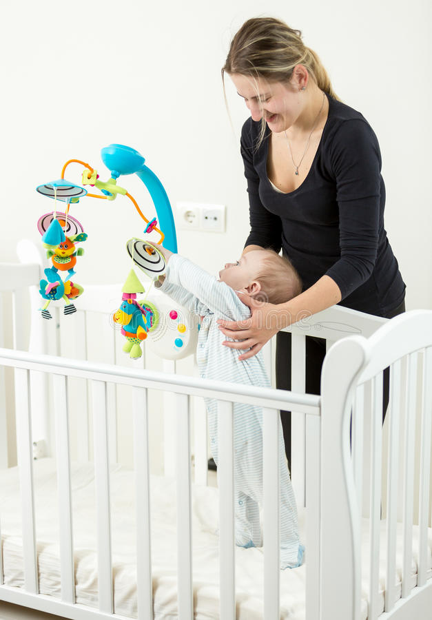 Young smiling mother standing at cot with her baby stock photos
