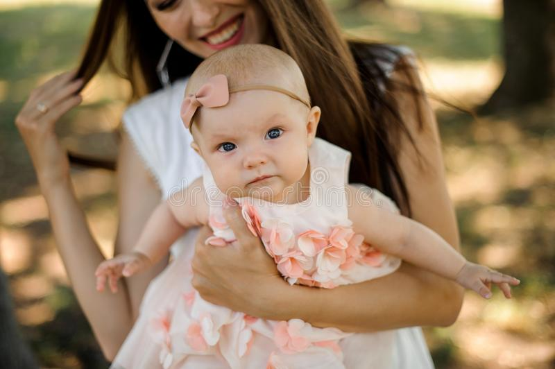 Young smiling mother walking with cute baby girl in park. Young smiling mother walking with cute blue-eyed baby girl in park on sunny summer day royalty free stock photos