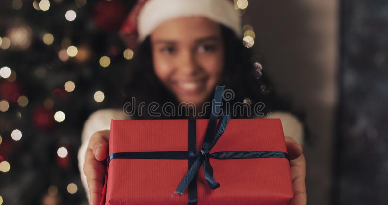 Young Smiling Girl in Santas Hat Gives the Red Present Box with Blue Ribbon to Camera, Standing at Christmas Tree royalty free stock image