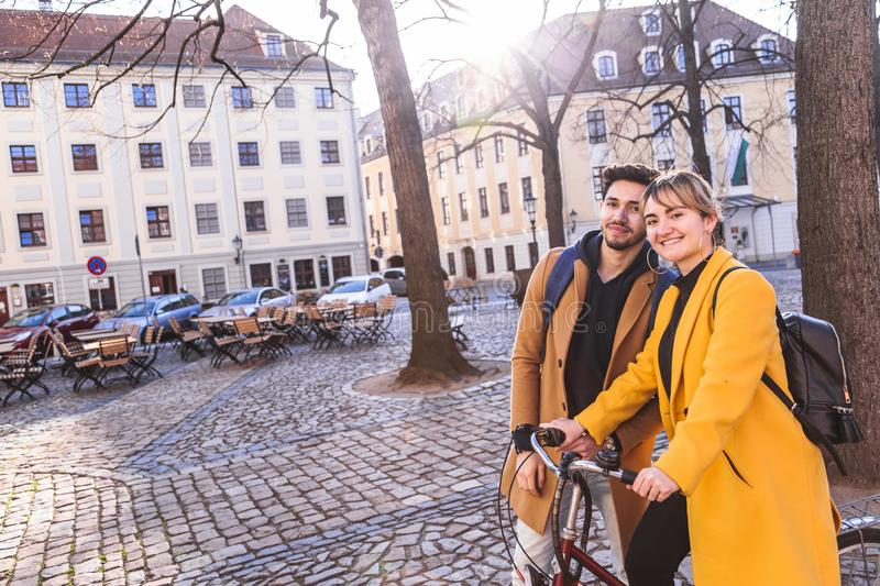 Young smiling multicultural couple with bicycle looking in camera stock image