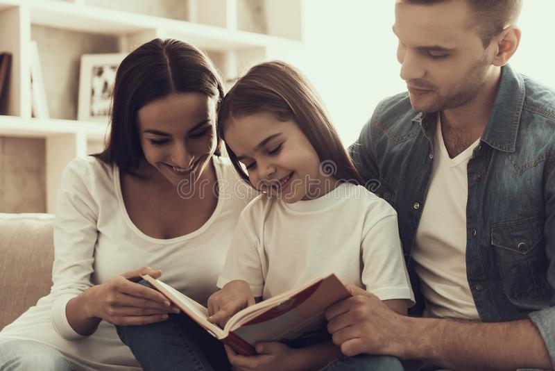 Young Smiling Parents Reading Book to Little Girl royalty free stock photography