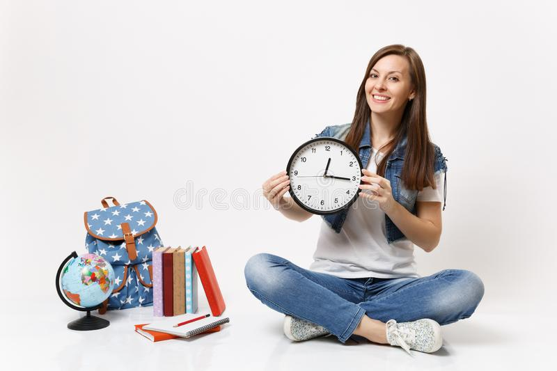 Young smiling pleasant woman student in denim clothes holding alarm clock sitting near globe, backpack, school books stock photo