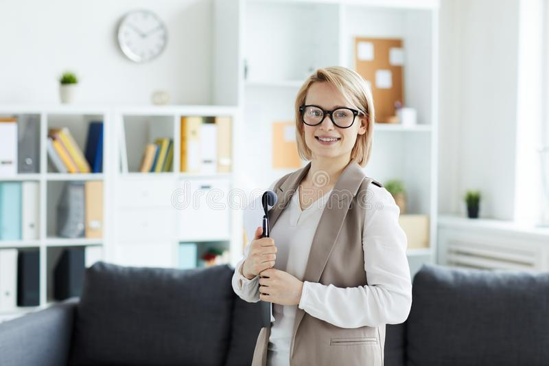 Counselor with paper. Young smiling pretty blonde standing in front of camera in her officewhile waiting for another patient stock image