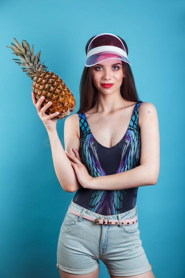 Young smiling pretty girl in plastic visor holding pineapple and posing on the blue background royalty free stock photo