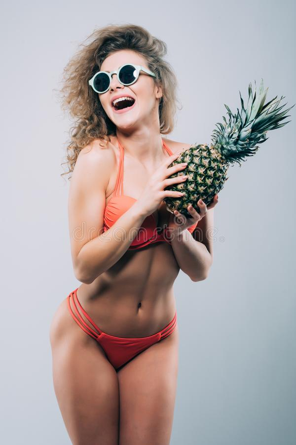 Young smiling pretty girl in sunglasses holding pineapple with porfect body isolated on the white background stock images