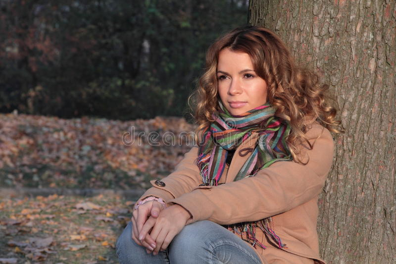 Young, smiling and pretty woman in the autumn park royalty free stock photos