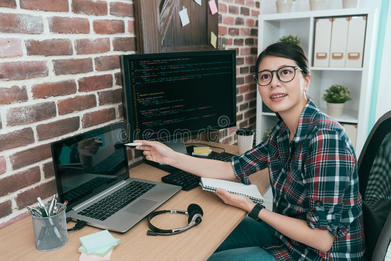 Young smiling programmer manager pointing laptop. Development plan document talking with colleague and meeting together discussing design data stock image