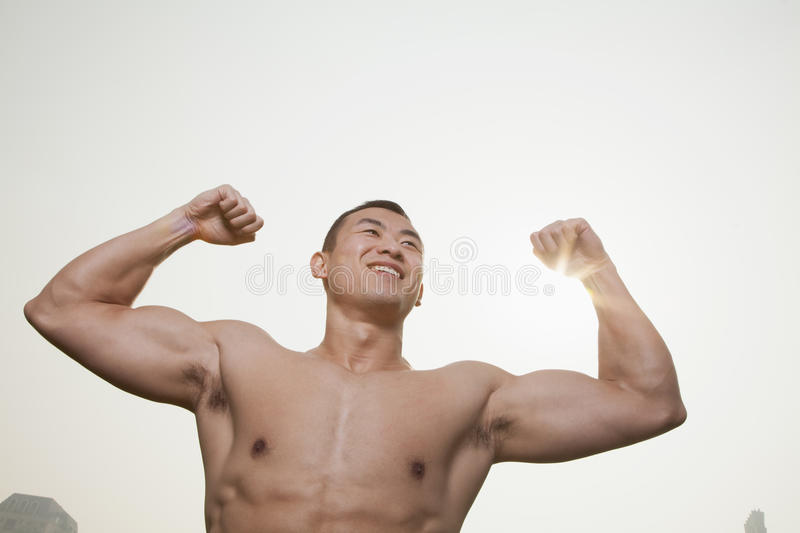 Young, smiling, shirtless young man flexing his muscles with arms raised outdoors in Beijing, China stock photo