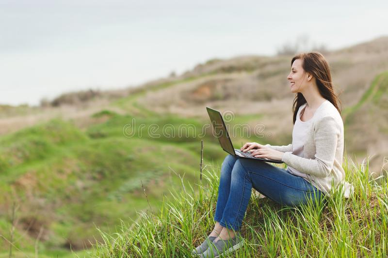 Young smiling successful smart business woman or student in light casual clothes sitting on grass using laptop in field stock photos