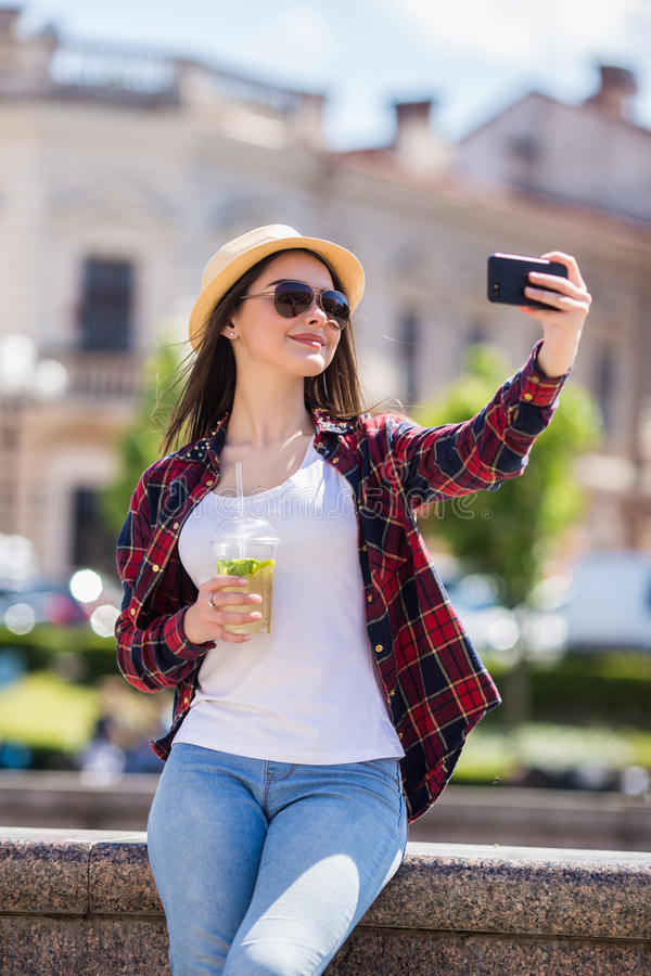 Young smiling teen happy woman making selfie. On the street royalty free stock images