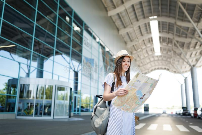 Young smiling traveler tourist woman with backpack holding paper map at international airport. Female passenger. Traveling abroad to travel on weekends getaway stock photo
