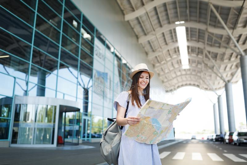 Young smiling traveler tourist woman with backpack holding paper map at international airport. Female passenger. Traveling abroad to travel on weekends getaway stock photos