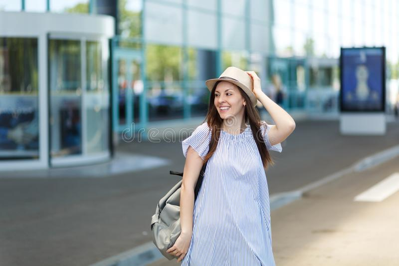 Young smiling traveler tourist woman in hat with backpack standing at international airport. Female passenger traveling. Abroad to travel on weekends getaway stock photography