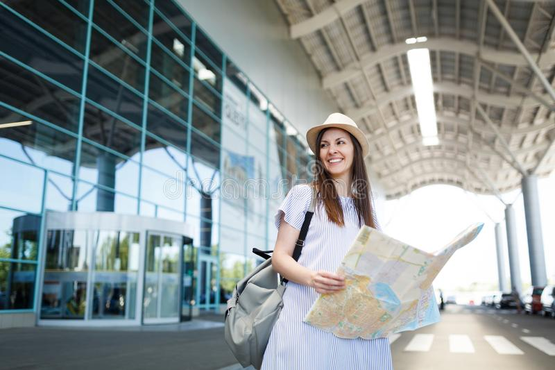 Young smiling traveler tourist woman in hat, light clothes hold paper map at international airport. Female passenger. Traveling abroad to travel on weekends stock photos