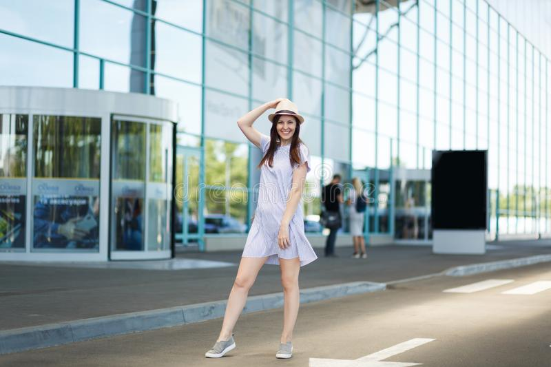 Young smiling traveler tourist woman in hat and light clothes standing at international airport. Female passenger. Traveling abroad to travel on weekends stock photo