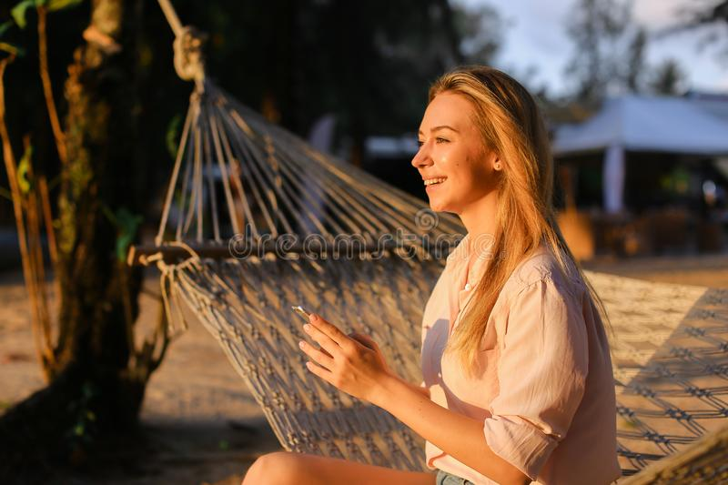 Young smiling woman using smartphone and sitting in wicker hammock on tropical resort. royalty free stock photo