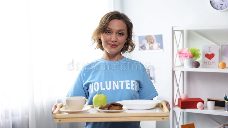 Young smiling volunteer holding tray with breakfast food in hands, kindness royalty free stock photo