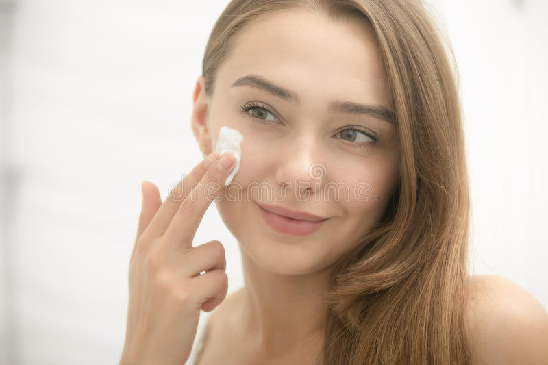 Young smiling woman applying cream to face in the bathroom. Young smiling woman applying cream to her face and looking at the mirror at home bathroom. Beauty stock photography