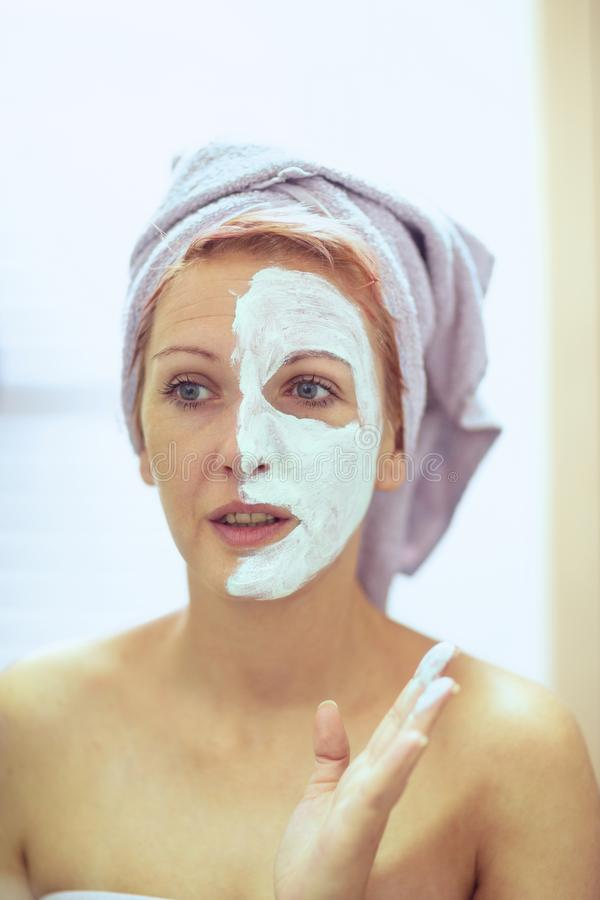 Smiling Woman applying facial mask. Beauty treatments stock photo
