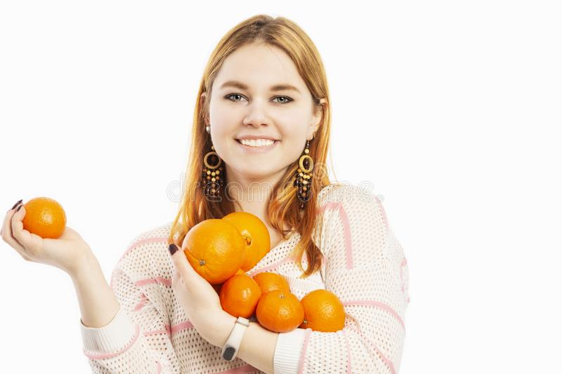Young smiling woman with an armful of oranges royalty free stock photo