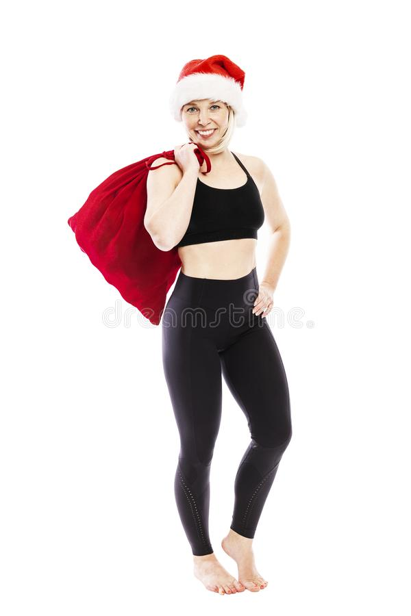 Young smiling woman in a black tracksuit in a Santa Claus hat and a red bag with gifts. Full height. Isolated over white stock photos