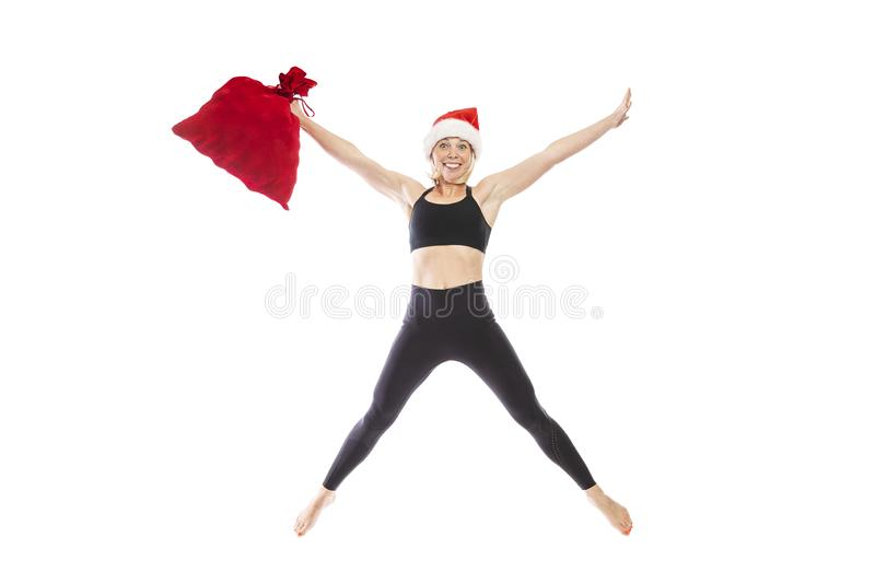 Young smiling woman in a black tracksuit in a Santa Claus hat and a red bag with gifts is jumping. Full height. Isolated over royalty free stock image