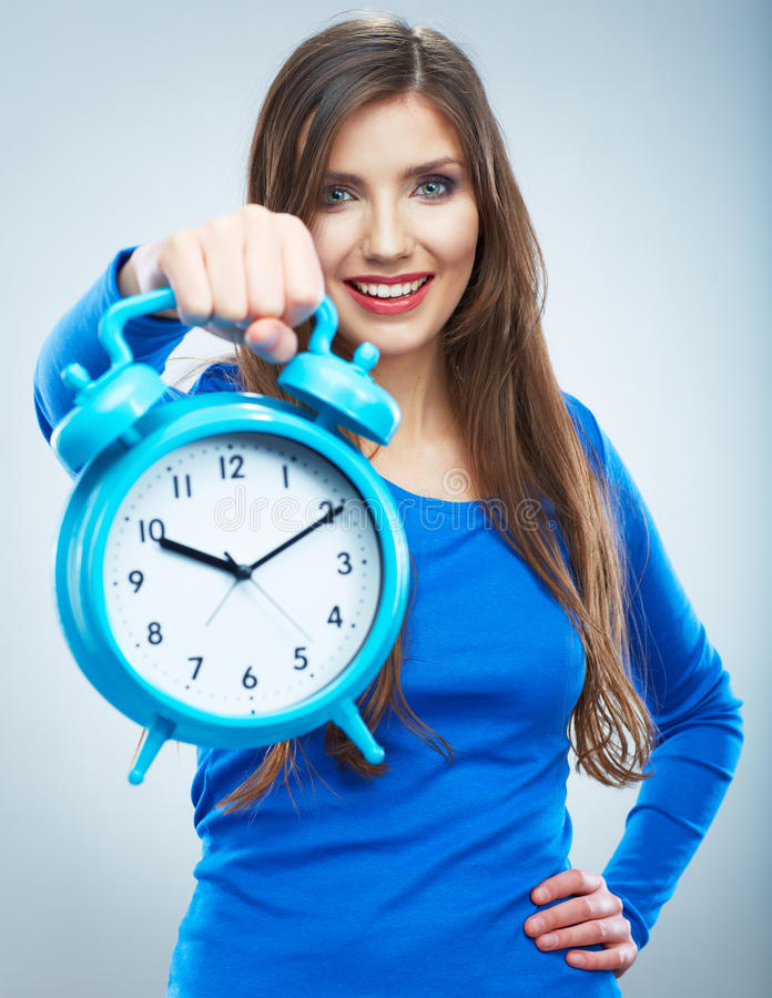 Young smiling woman in blue hold watch. Beautiful smiling girl. Portrait. Isolated studio background female model royalty free stock images