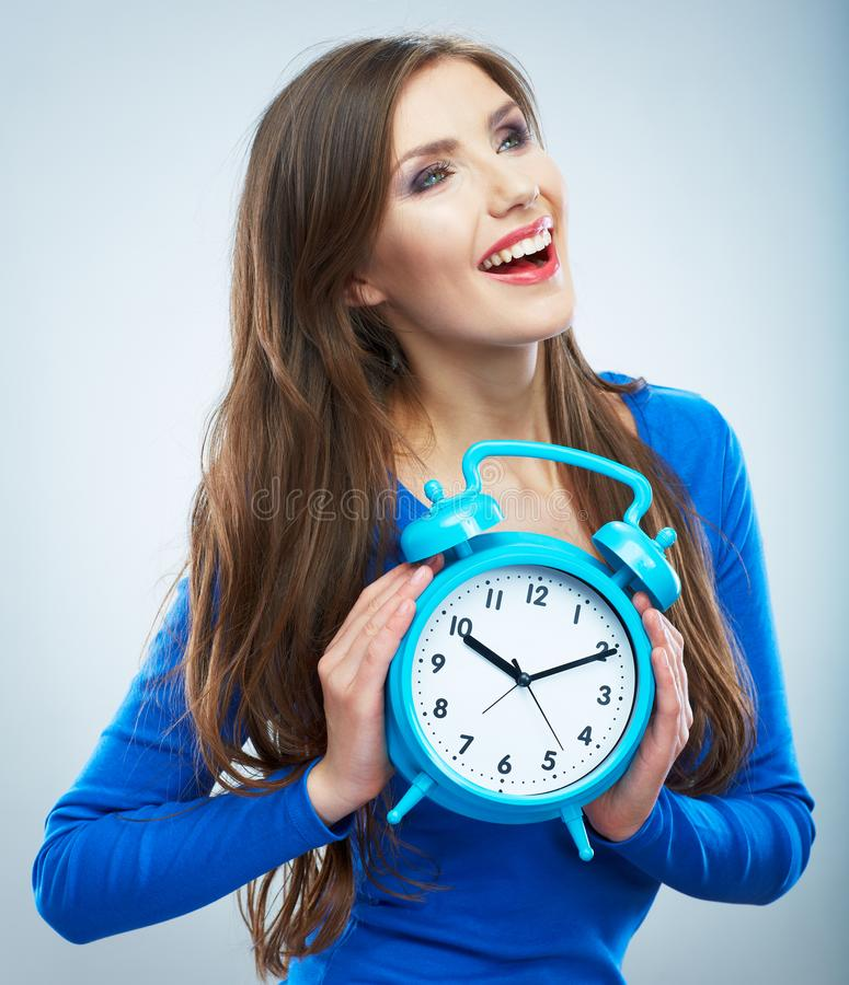 Young smiling woman in blue hold watch. Beautiful smiling girl. Portrait. studio background female model royalty free stock photo