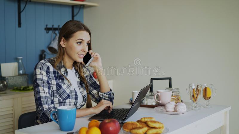 Young smiling woman browsing social media using laptop computer and talking phone during breakfast in the morning stock photo