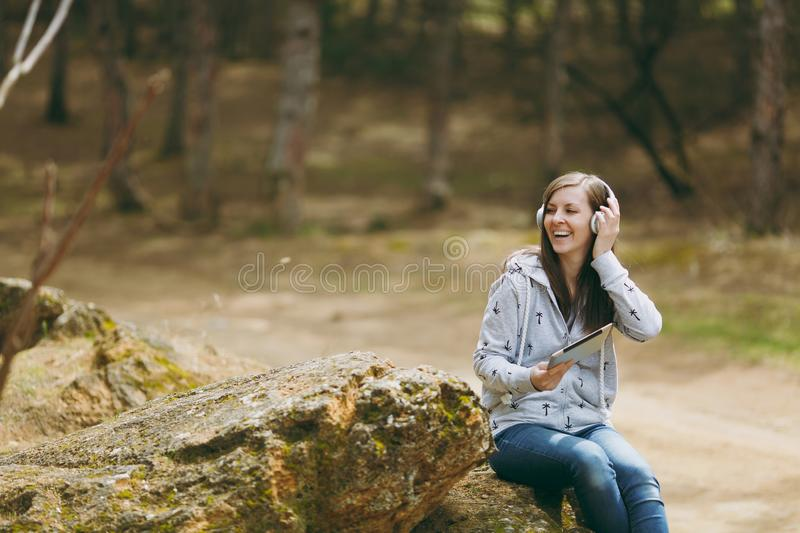 Young smiling woman in casual clothes sitting on stone listening music with headphones and tablet pc computer in city. Park or forest on green blurred royalty free stock image