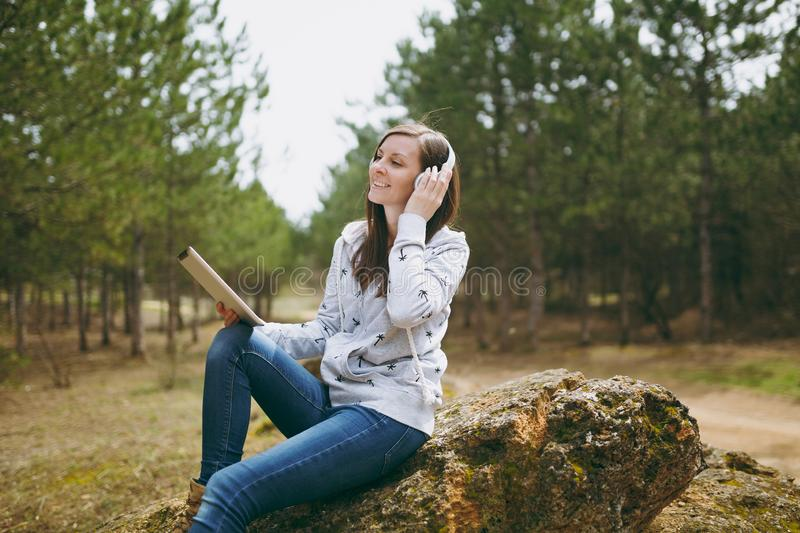 Young smiling woman in casual clothes sitting on stone listening music with headphones and tablet pc computer in city. Park or forest on green blurred royalty free stock images