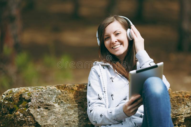 Young smiling woman in casual clothes sitting on stone listening music with headphones and tablet pc computer in city. Park or forest on green blurred royalty free stock photos