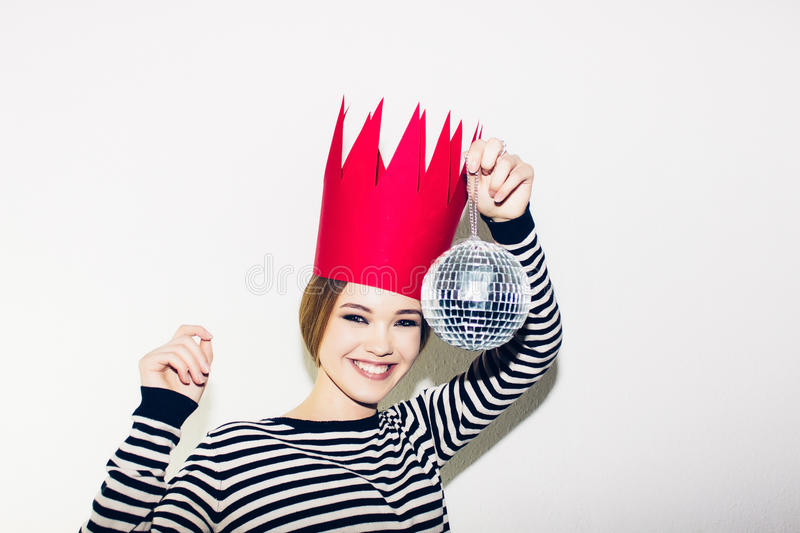 Young smiling woman celebrating party, wearing stripped dress and red paper crown, happy dynamic carnival disco ball. Young smiling woman on white background royalty free stock images